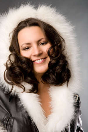 curly-headed woman in leather coat on grey background photo