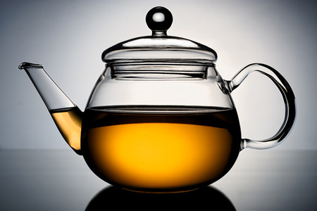 Glass teapot with the infusion of tea in the light gradient background  photo