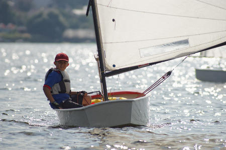 yachtsman: Young yachtsman manages dinghies Optimist.