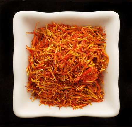 Spice saffron in a ceramic bowl. Isolated on black. photo