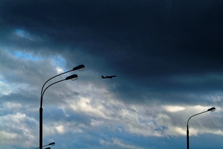 the plane in the storm sky in the evening, in Moscow