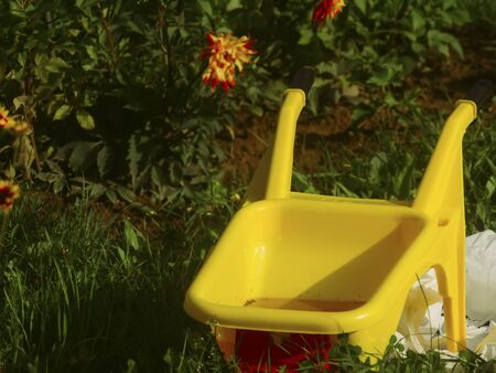 yellow plastic children's wheelbarrow in the garden, Russia Stok Fotoğraf