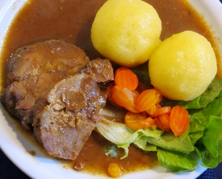 Traditional german Spießbraten with sauce and cooked potato dumplings