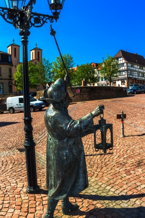 Lantern lighter sculpture in medieval city center of Gelnhausen, Germany, the geographic center of the European Union in 2010 Stock Photo - 25220020