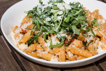 Rigatoni with spicy rucola salad, shrimp and parmesan cheese