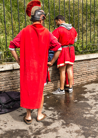 actors: Roman warrior actors changing clothes on a street in Rome