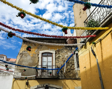 bairro: Lisbon old town houses decorated with flowerpots and garlands at Easter