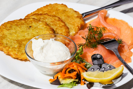 Delicious potato pancakes with smoked salmon and horseradish sauce