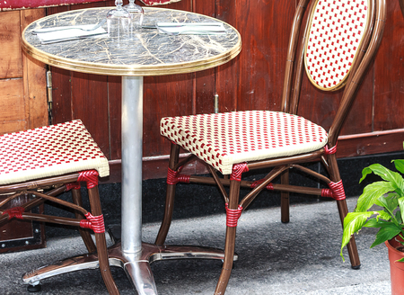 #64557067   Small Round Table With Two Red And White Chairs In Traditional  Outside Cafe In Paris, France