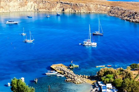 Beautiful small closed port of St. Paul beneath the rocks of Acropolis of Lindos with its blue waters and white boats, Rhodes Iceland, Greece