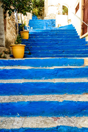 greek pot: Picturesque steep alleyway withblue panted steps in town on the Greek Iceland of Symi, Greece Archivio Fotografico