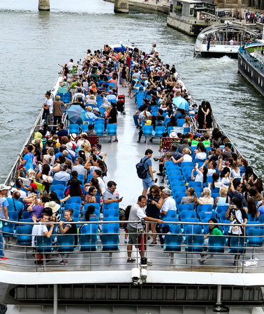 Tourist boat with blue chairs on the river Seine in Paris, France
