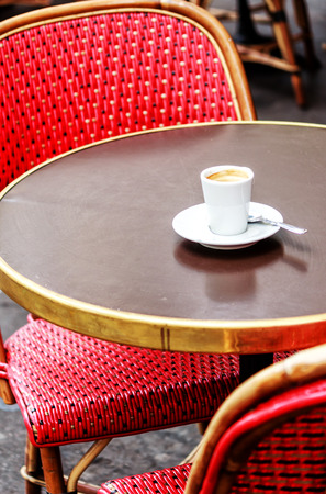 Parisian cafe with red wicker chairs and an espresso on the table Stock Photo