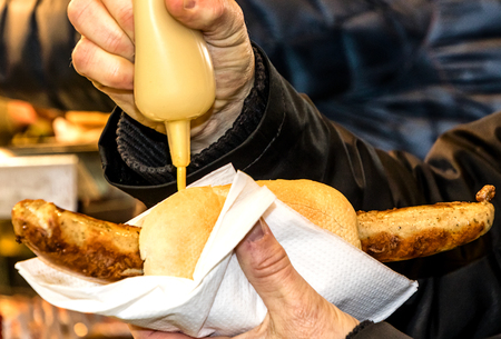 Typical german thuringian grilled sausage with mustard in the hand Standard-Bild