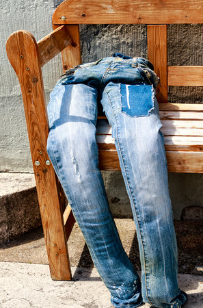 Stuffed blue jeans? Seated? on the wooden bench