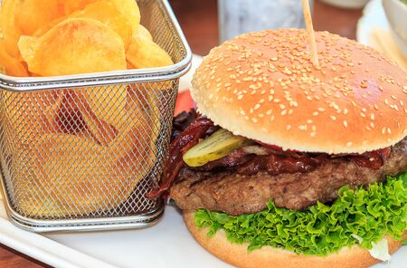 Tasty burger and homemade chips in a small net basket.