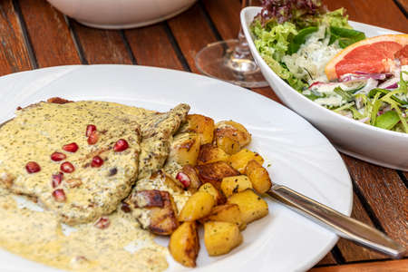 Pork Cutlet with wine - cream - herbs - sauce with fried potatoes and mixed salad