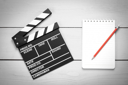 Clapper movie with note pad on wood background Stock Photo