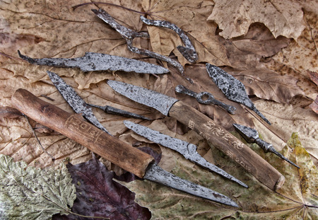 iron oxides: old knives and tips on a background of dry leaves