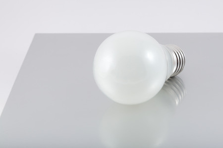 volts: the glow lamp lies on a gray flat surface Stock Photo