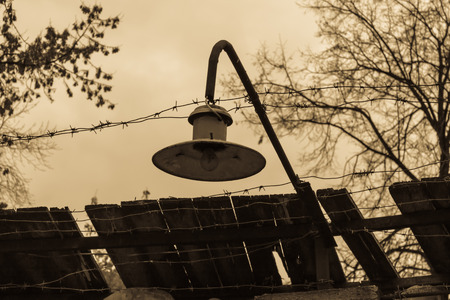 oppression: barbed wire and a night lamp on a wooden fence Stock Photo