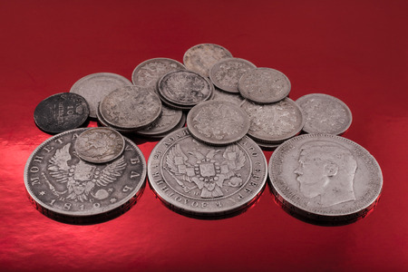 silver coins: old silver coins of the Russian Empire lie on red