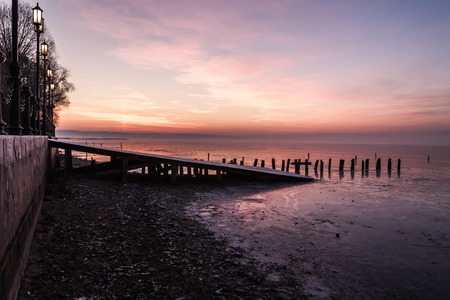 old pier: Sunset on the frozen old pier in early winter Stock Photo