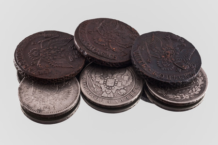 silver and copper coins with double headed eagle on the gray background are