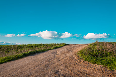 unpaved road: simple rural landscape with the unpaved road going directly to clouds