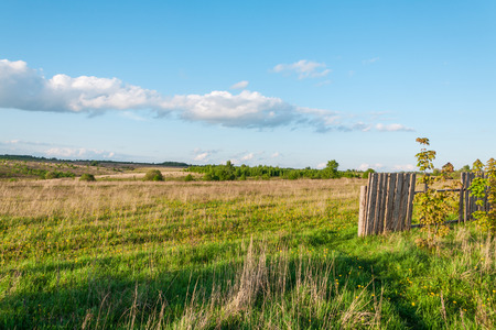 not full: hilly Russian landscape with not sowed fields and a fence full of holes