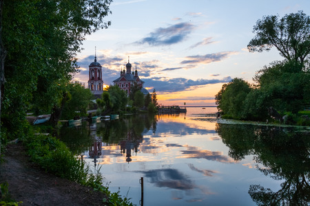 the decline: the mouth of the river in the summer evening against a decline and Christian church