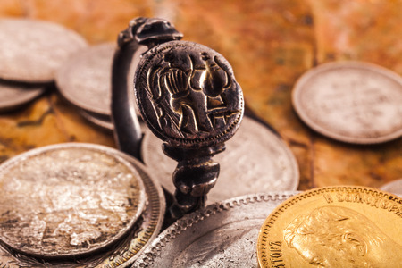 silver coins: medieval ring with the soldier and an amphora against dry leaves and silver and gold coins