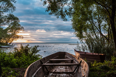 full of holes: the old boat full of holes is pulled out on the coast for dismantling on firewood for a fire or for the device of paths on the marshy coast Stock Photo