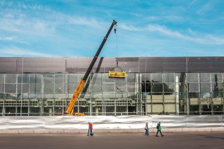 despacio: transeúntes solitarios lentamente van a lo largo de la construcción del edificio claro