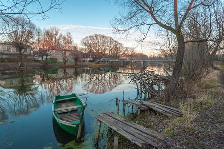 green boat: Pereslavl-Zalessky, Russia - November 07, 2015: The green boat on the parking at the river bank Trubezh late autumn evening.