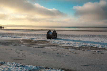 froze: The empty coil from a high-voltage cable froze in ice near the coast.