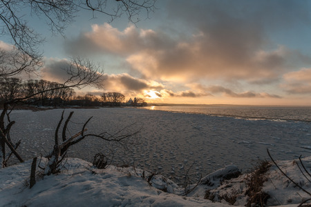 the decline: the cold decline on the bank of the lake contrasts with warm colors of the sky and the sun Stock Photo