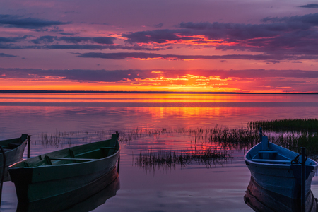 madly: Madly beautiful moment of sunset for the horizon against a water smooth surface and fishing boats Stock Photo