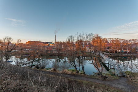without people: autumn landscape with a pipe, the river and the town without people