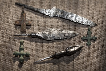 christian crosses: early medieval copper Christian crosses, iron tips of arrows and the forged knife Stock Photo