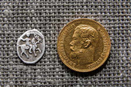 kopek: Two Russian coins - silver kopek of Ivan Grozny and gold five rubles of Nikolay Romanov.