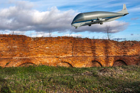 nasa: NASA Super Guppy, a wide-bodied cargo aircraft in the blue sky over a red brick wall. Elements of this image furnished by NASA. Collage.