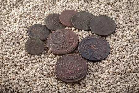 oxides: Copper Russian coins of 18-19 centuries in a patina and oxides on white coarse sand. Stock Photo