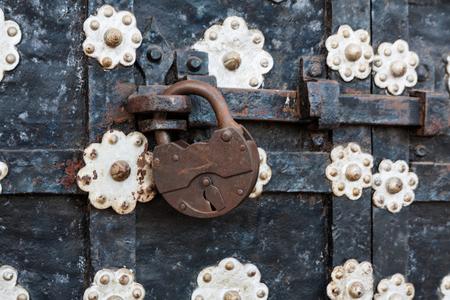 iron oxides: The rusty iron padlock hangs on an old metal door