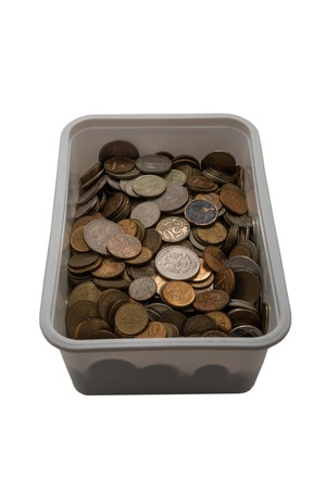 unnecessary: Light plastic box with unnecessary small coins on a white background. Stock Photo