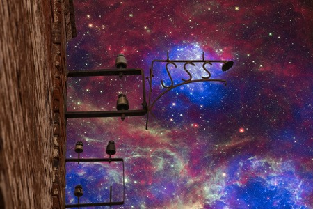 galaxies: the electric lamp of the end of the nineteenth century on an old brick wall against stars of far galaxies