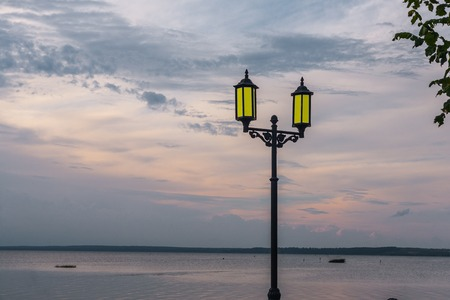 the decline: The yellow stylized semi-antique lamp burns in the last beams of a decline ashore