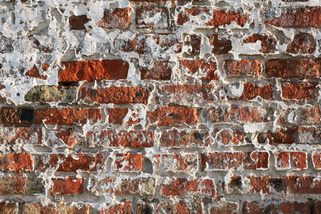 swept: Fragment of an old brick monastic wall with the fallen-off whitewashing in evening side lighting. Stock Photo