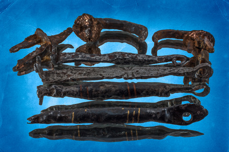 oxides: Fragments of iron medieval keys and padlocks approximately the 12th centuries on a blue mirror background.