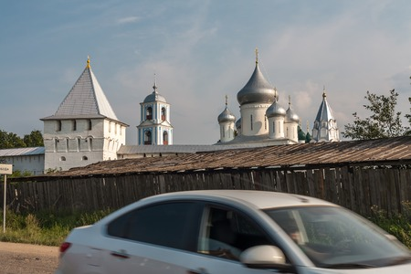 drove: the girl in dark glasses by white car promptly drove in a shot against the background of the Christian monastery